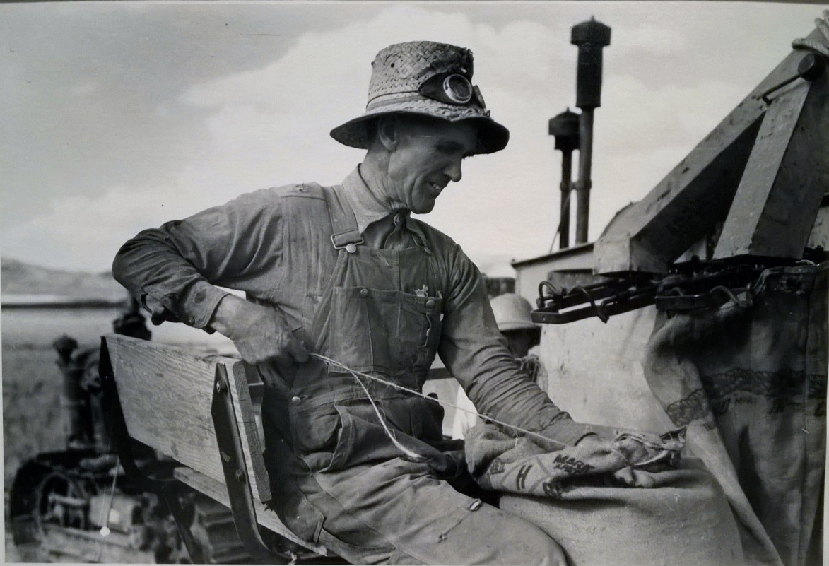 Russell Lee, Mormon farmer who lives in Snowville, Utah, and who farms in Oneida County, Idaho, Bagging Wheat, 1940